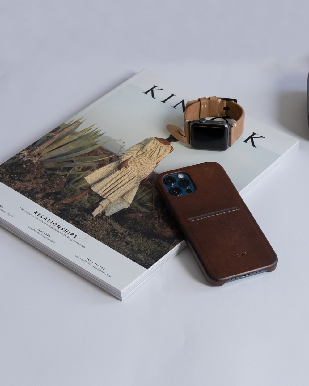 brown leather bifold wallet on white book page
