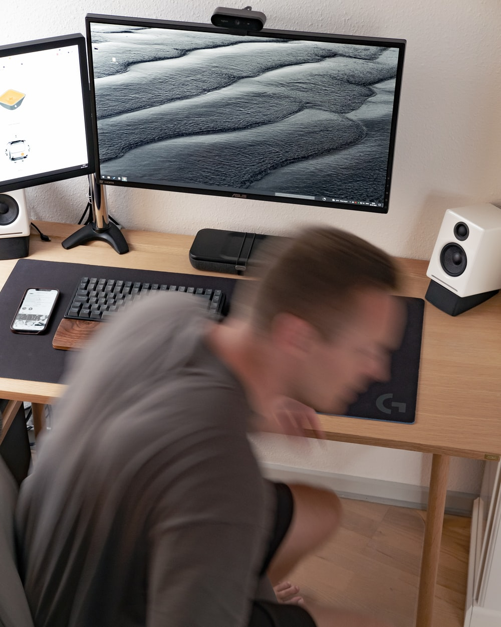 man in gray long sleeve shirt sitting in front of computer