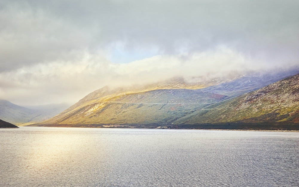 brown and green mountains beside body of water under white clouds during daytime