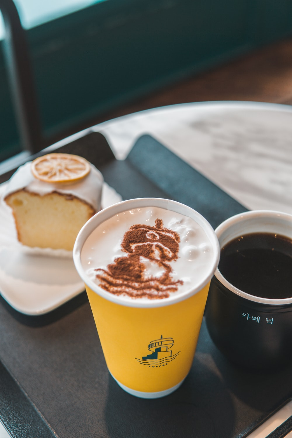 yellow and white disposable cup with coffee