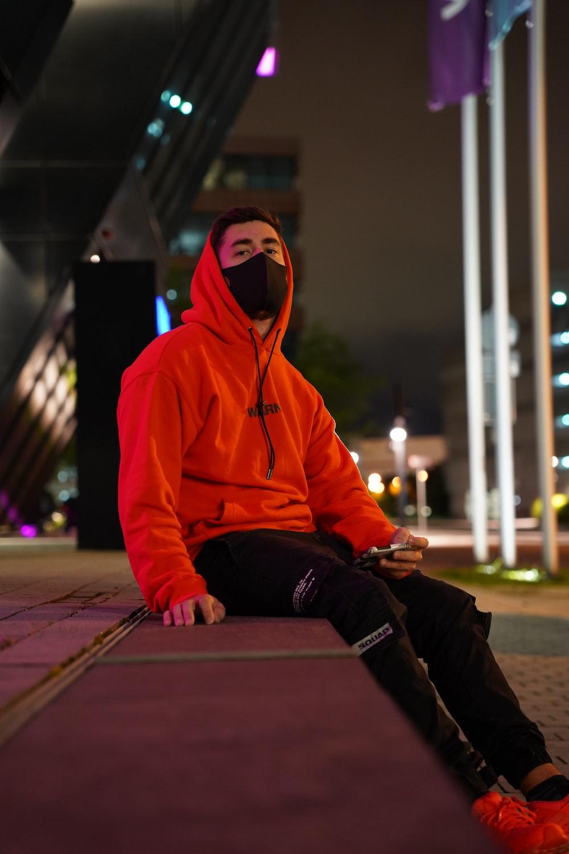 man in orange hoodie sitting on brown wooden floor