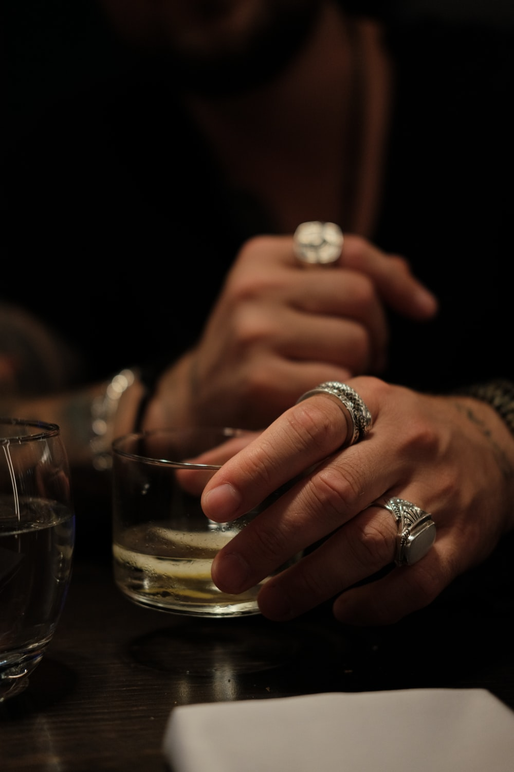 person wearing silver ring holding clear drinking glass
