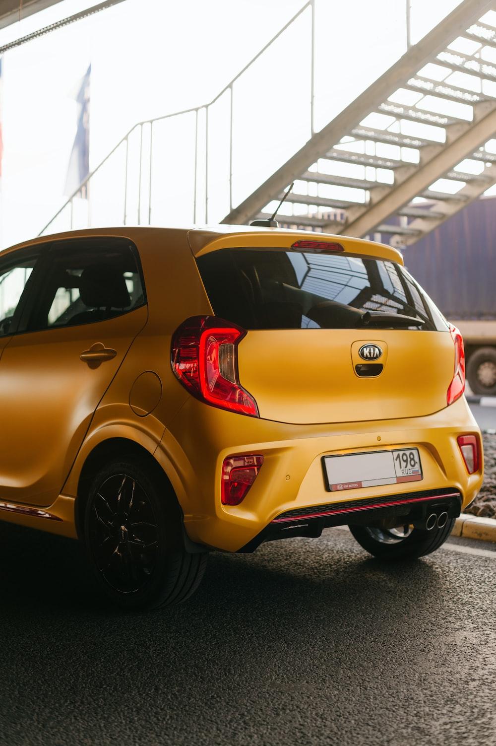 yellow 5 door hatchback parked on garage