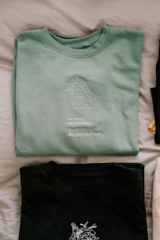 green crew neck shirt on white textile