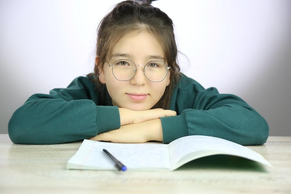 woman in green long sleeve shirt wearing eyeglasses