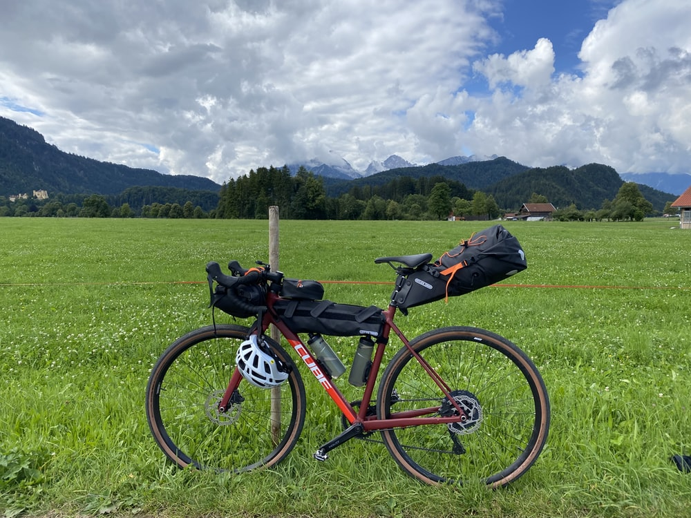 red and black mountain bike on green grass field during daytime