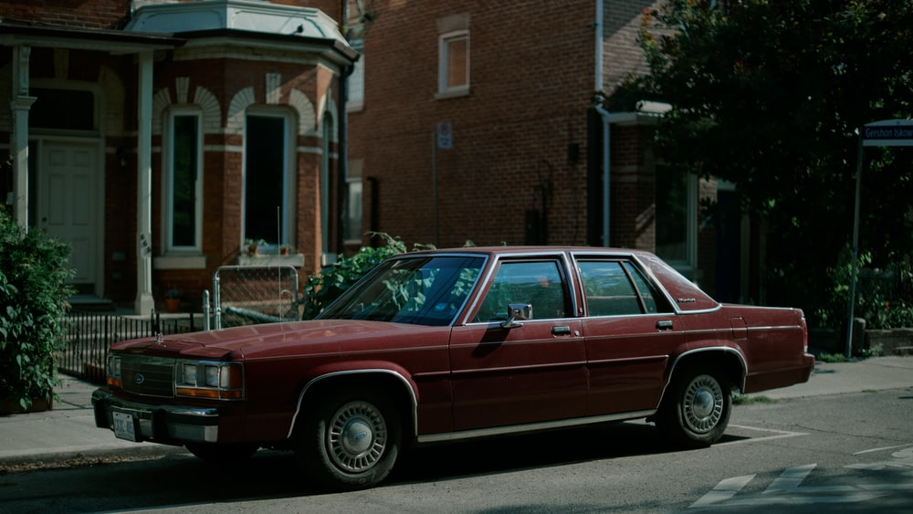 red and white station wagon parked beside brown concrete building during daytime