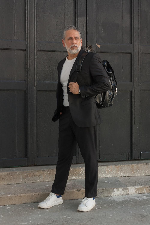 man in black blazer standing near black wooden door