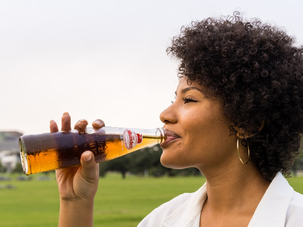 woman drinking coca cola bottle