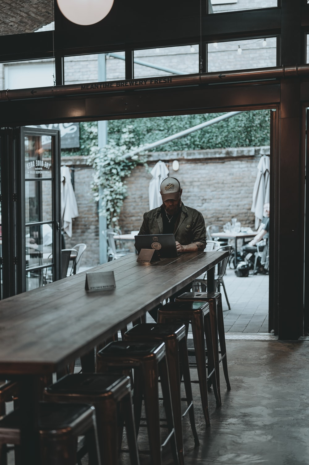 man in black jacket sitting on chair near table