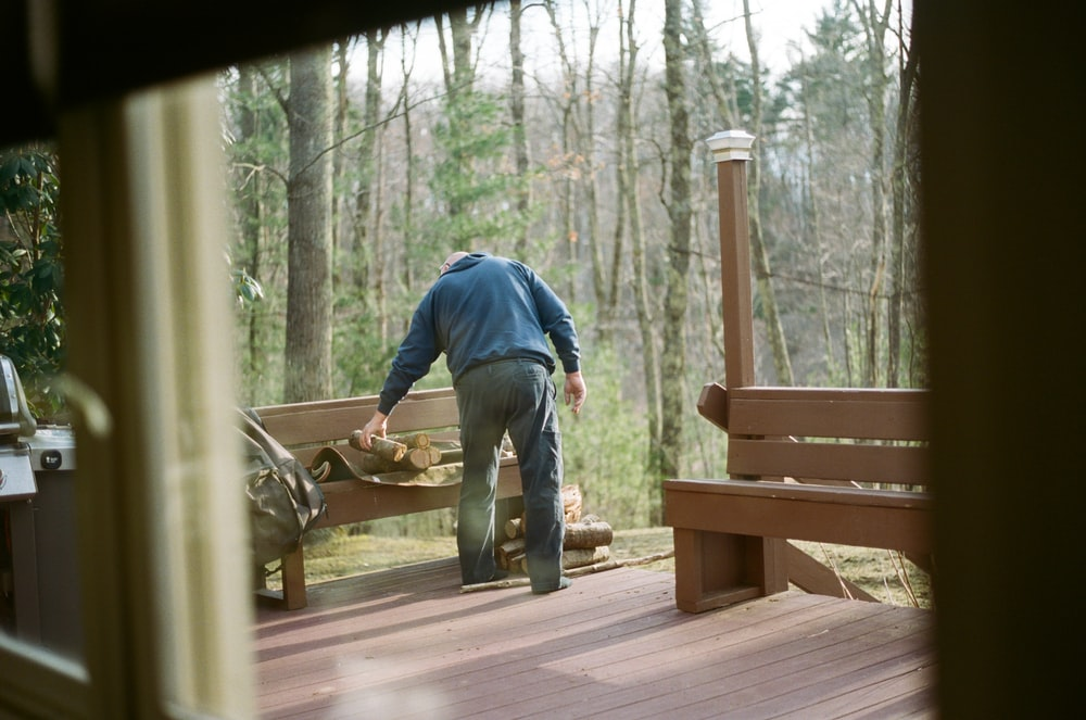 man in blue jacket and gray pants standing on brown wooden bridge