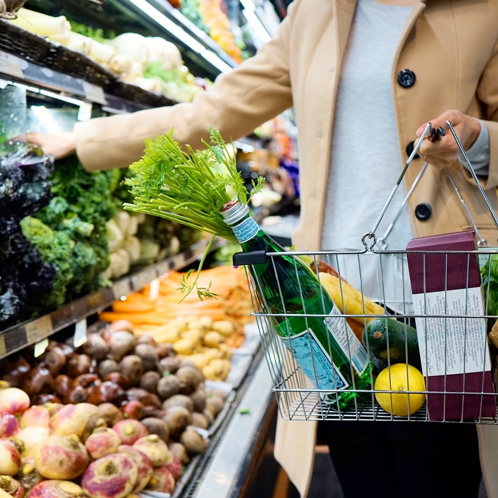 woman in white coat holding green shopping cart