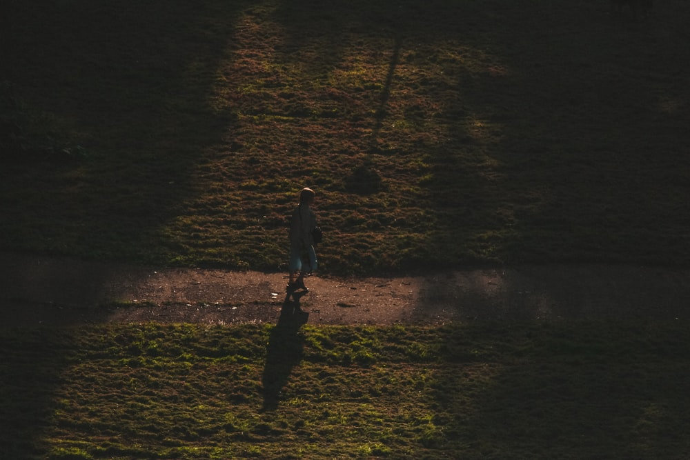 person in black jacket walking on brown field during night time