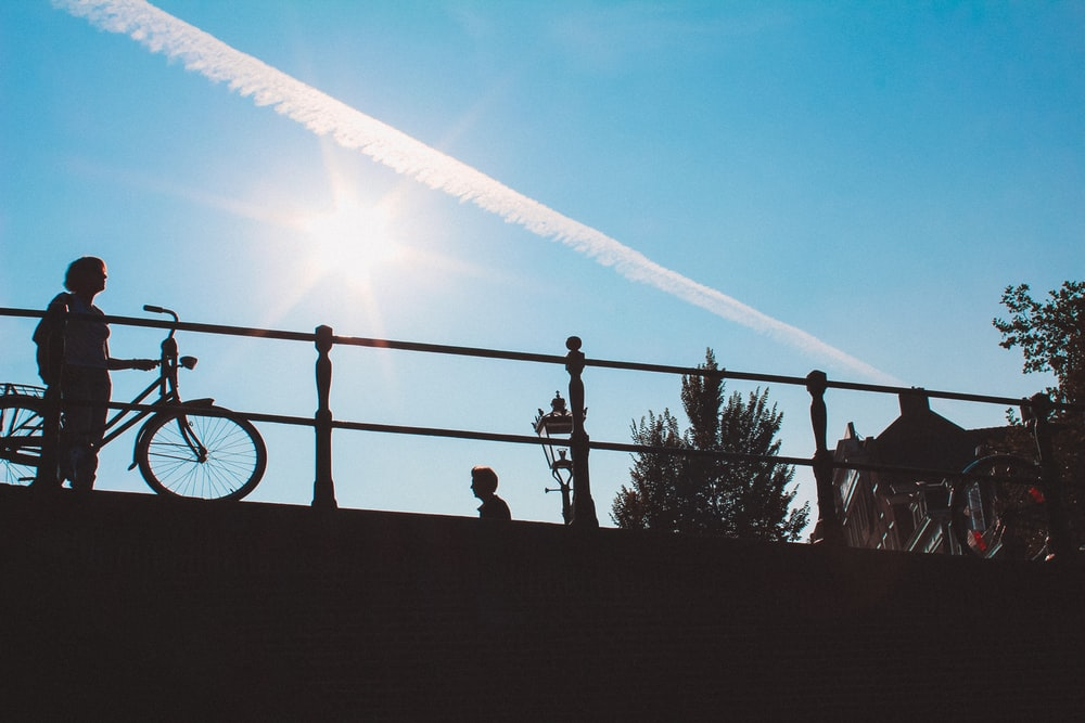 silhouette of person standing on black metal fence during daytime