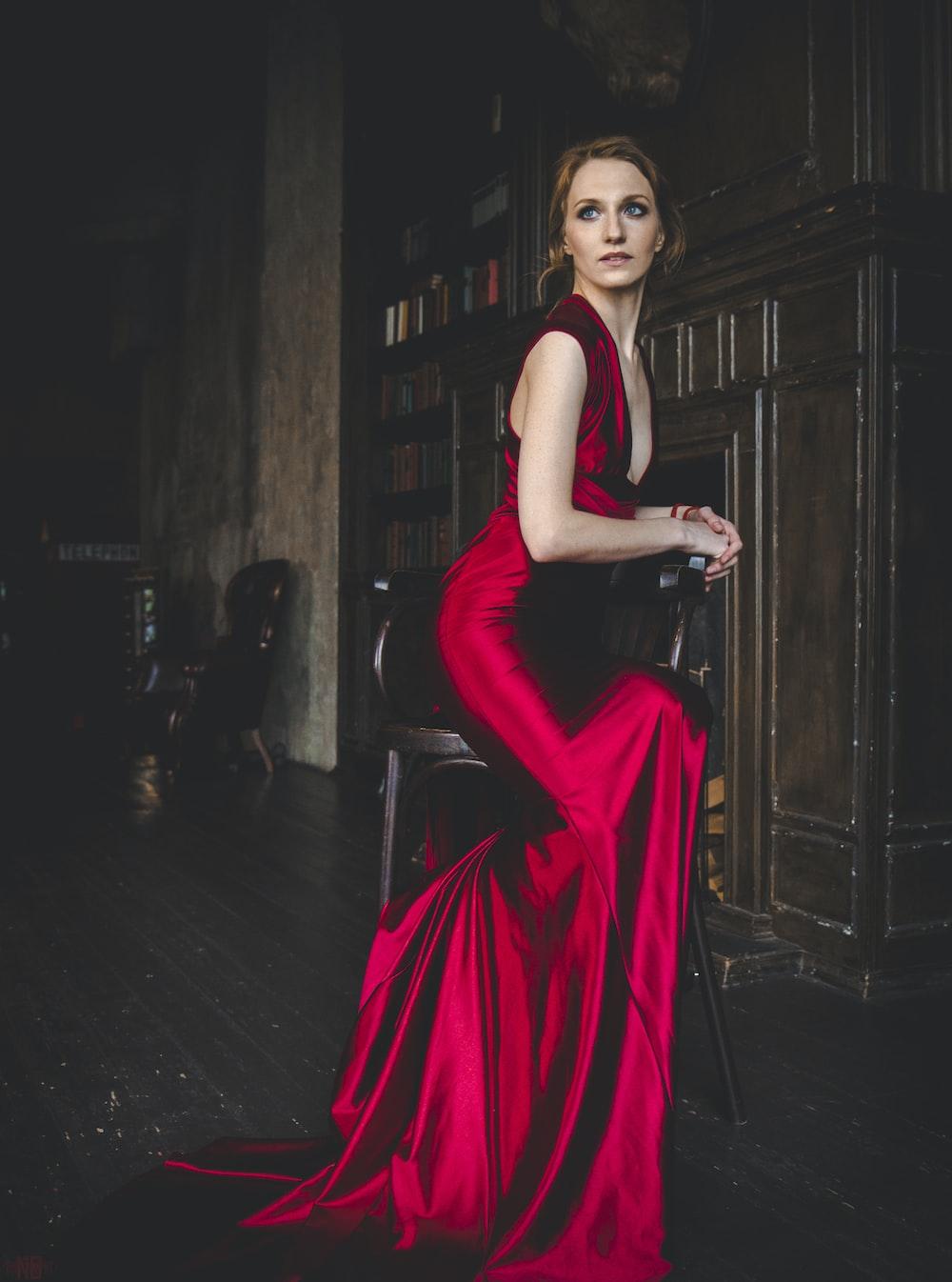 woman in red sleeveless dress standing on black floor