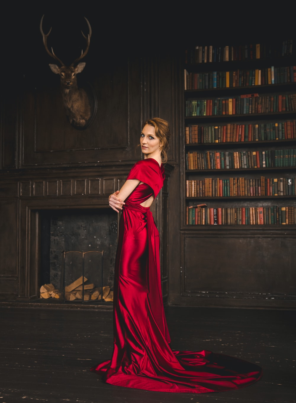 woman in red long sleeve dress standing beside brown wooden book shelf