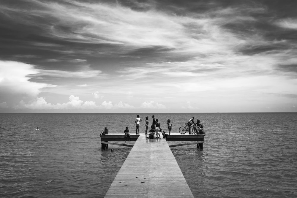 grayscale photo of people walking on wooden dock