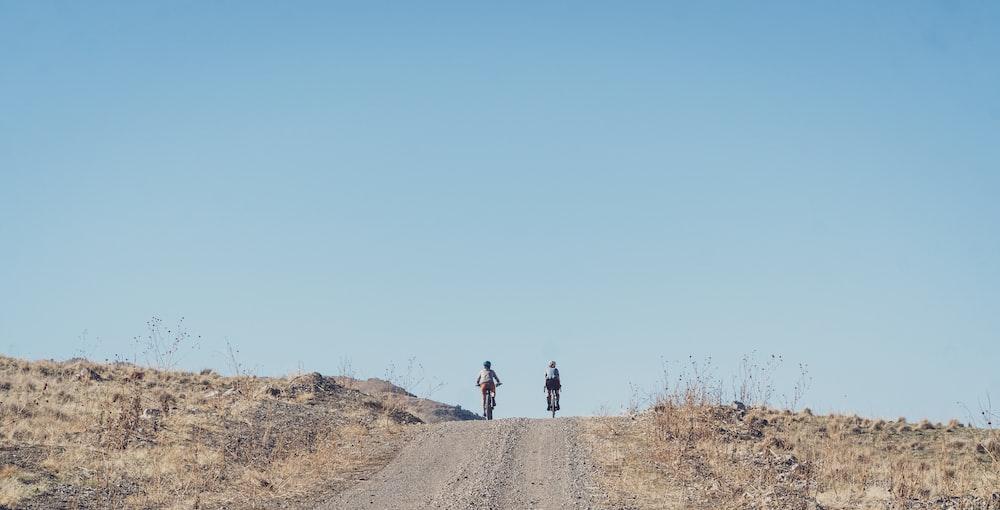 man in black jacket and black pants walking on brown dirt road during daytime