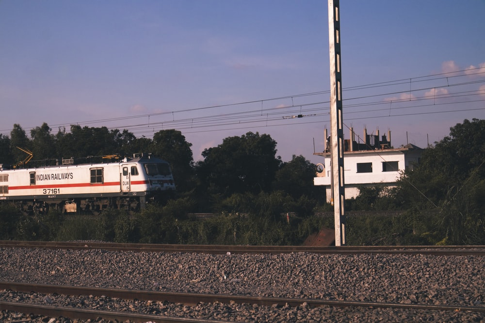 white and red train on rail tracks