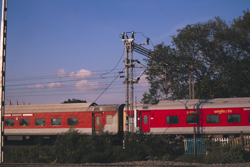 red and white train on rail under blue sky during daytime