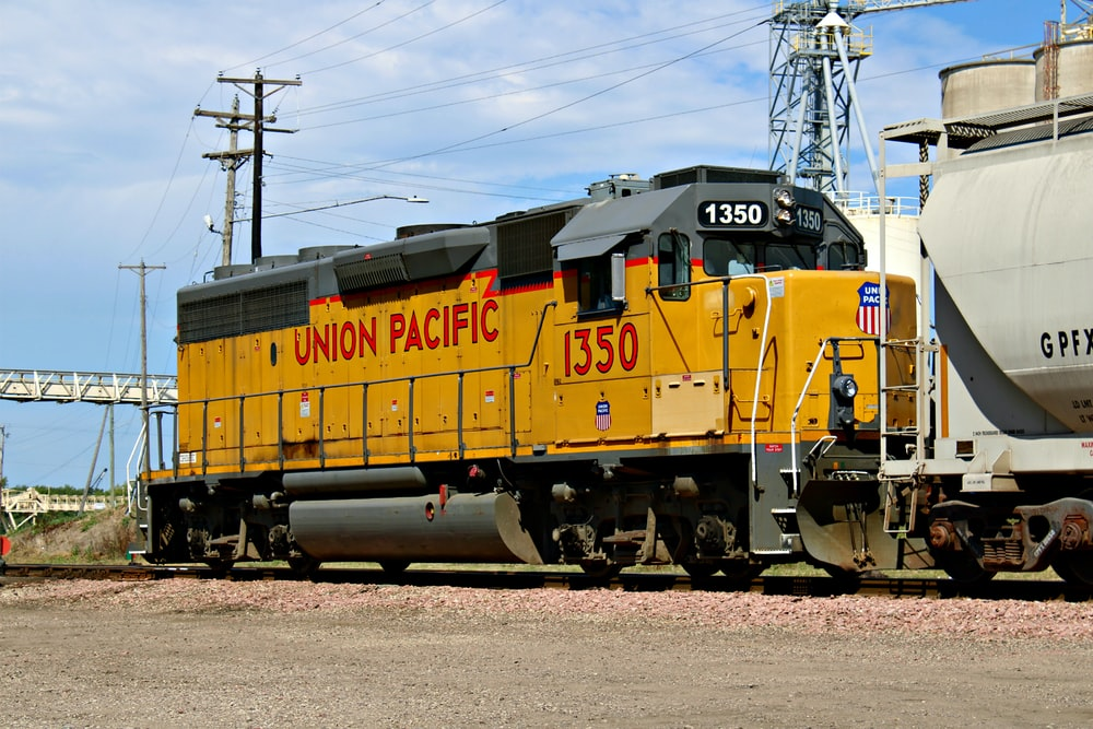 yellow and black train on rail tracks under blue sky during daytime
