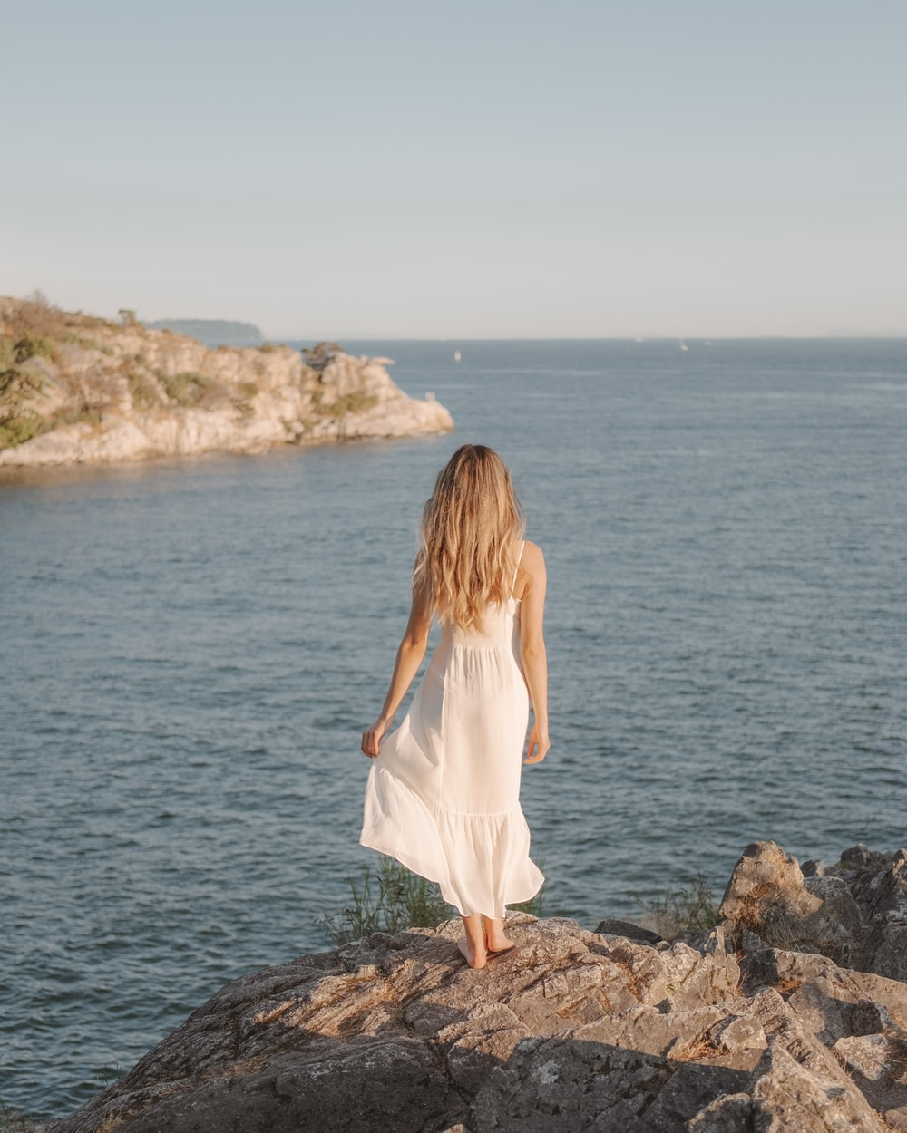 woman in white dress standing on rock near body of water during daytime