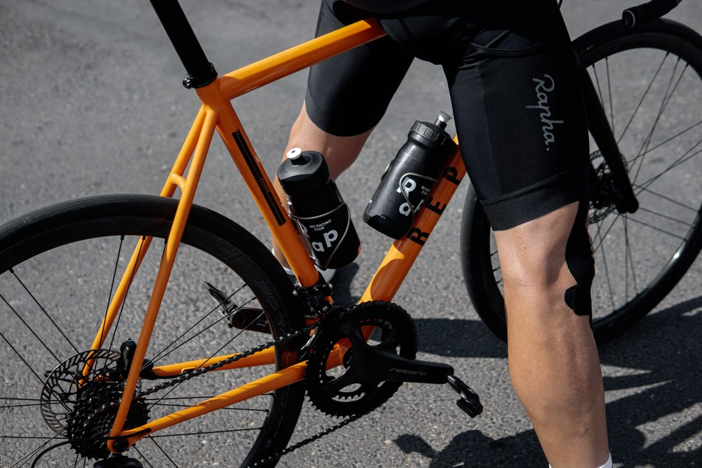 person in black shorts and black nike shoes riding orange and black bicycle