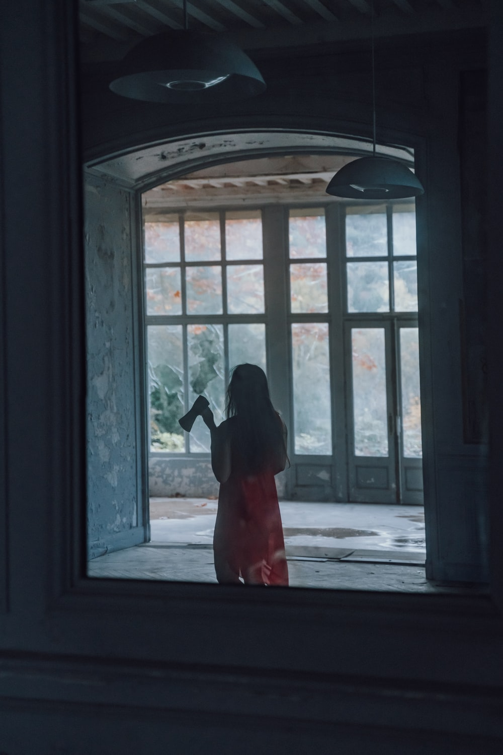 woman in red dress standing in front of window