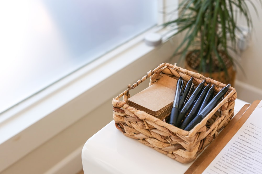 black and white pen in brown woven basket