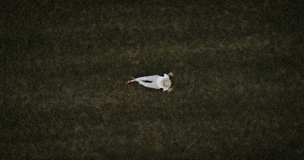 woman in white long sleeve shirt lying on green grass field during daytime