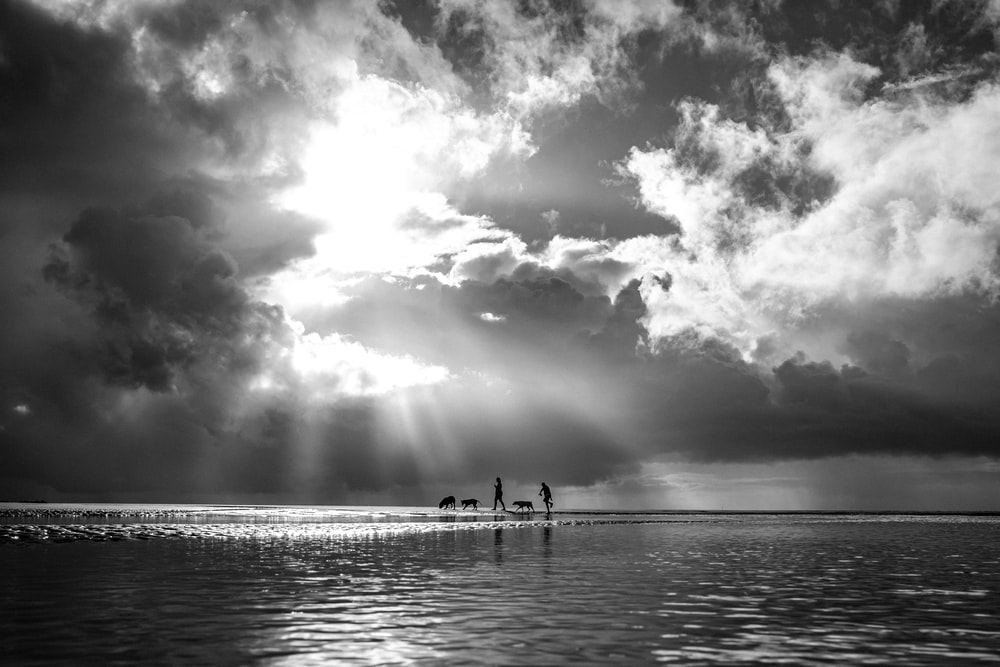 grayscale photo of people on sea under cloudy sky