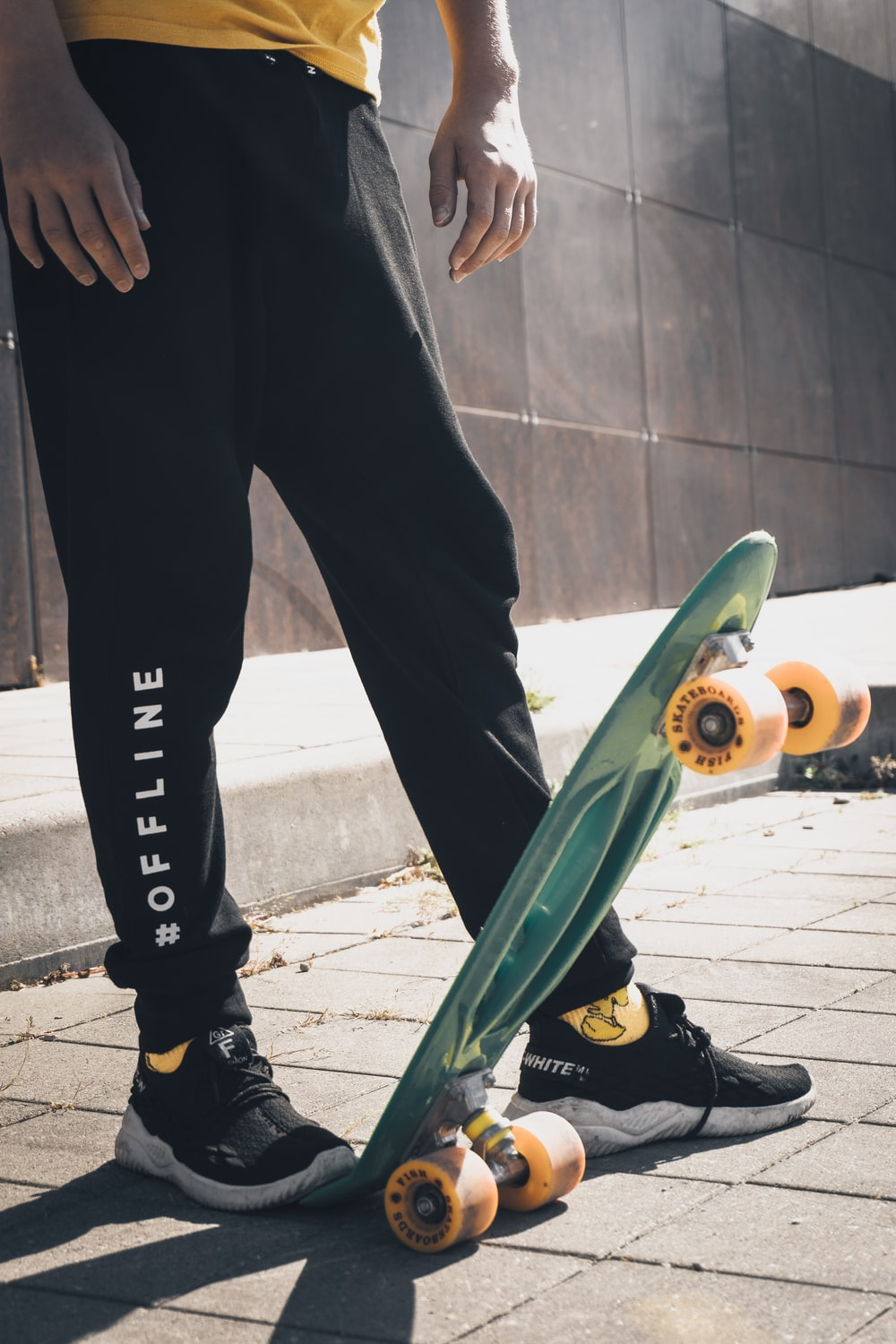 person in black pants and black nike shoes holding green skateboard