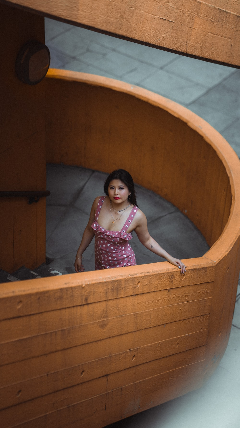 girl in pink and white floral dress in brown wooden bathtub