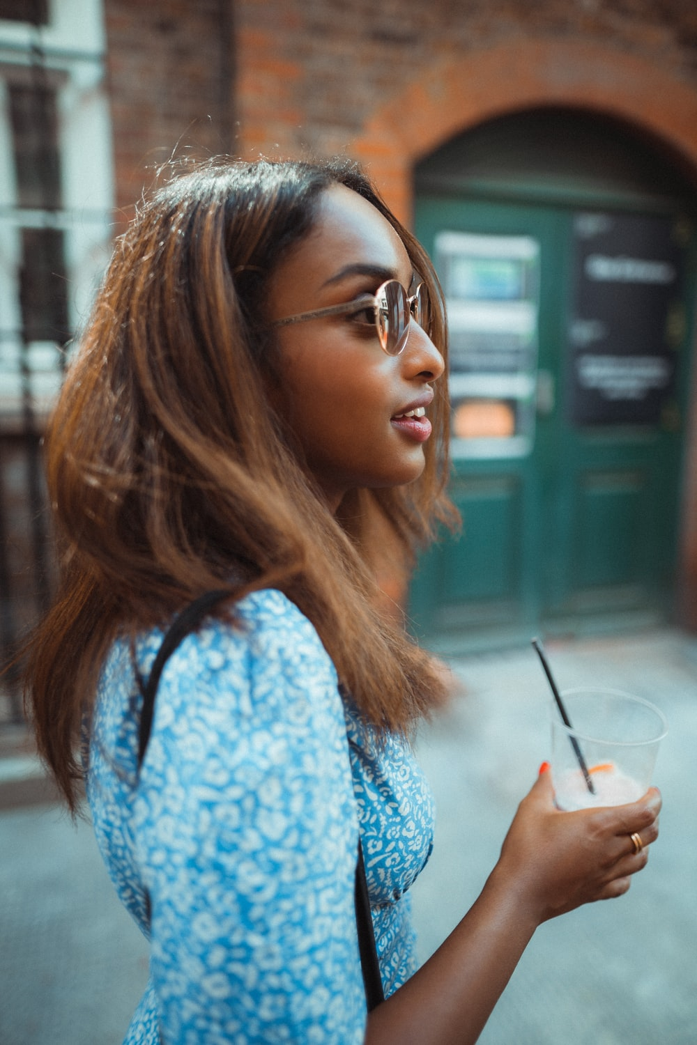 woman in blue and white floral shirt holding white disposable cup