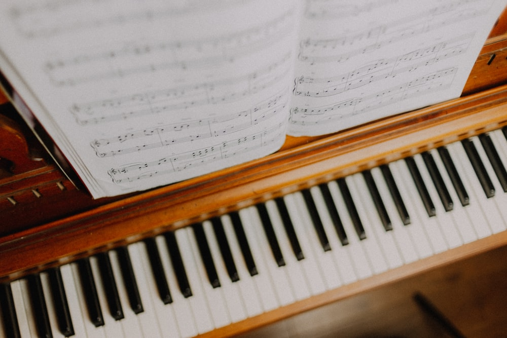 musical notes on brown upright piano