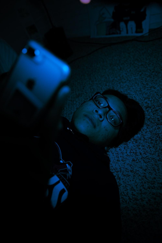 boy in black framed eyeglasses lying on floor