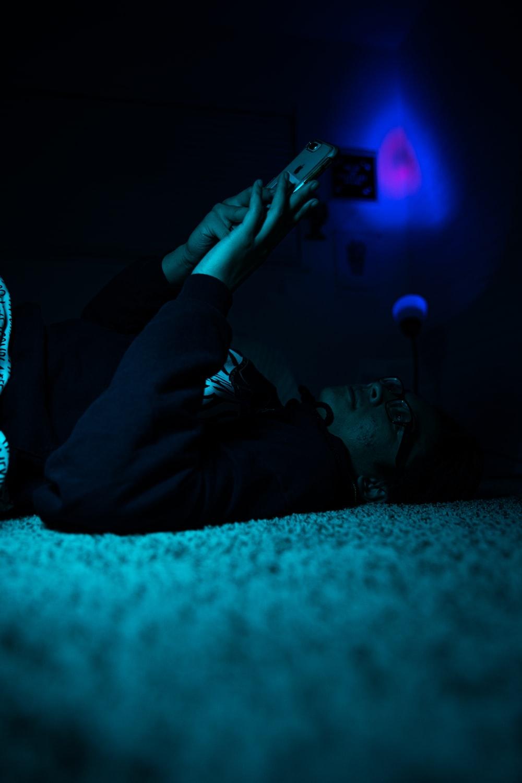 man in black pants lying on floor