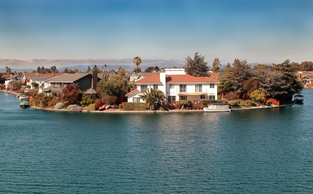 white and brown concrete house near body of water during daytime