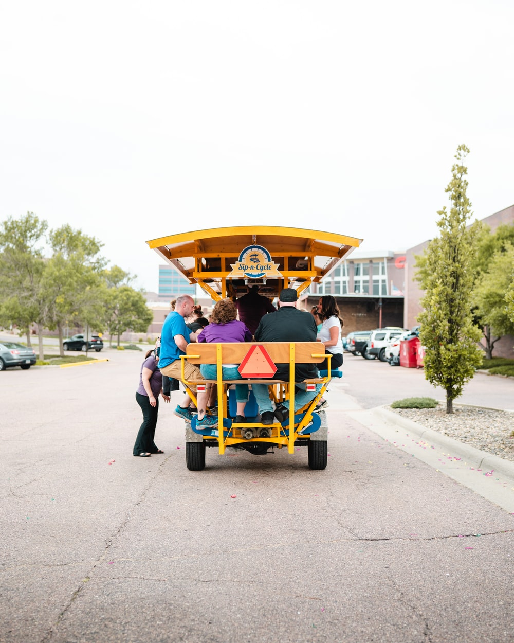 man in blue shirt riding yellow and red cart on road during daytime