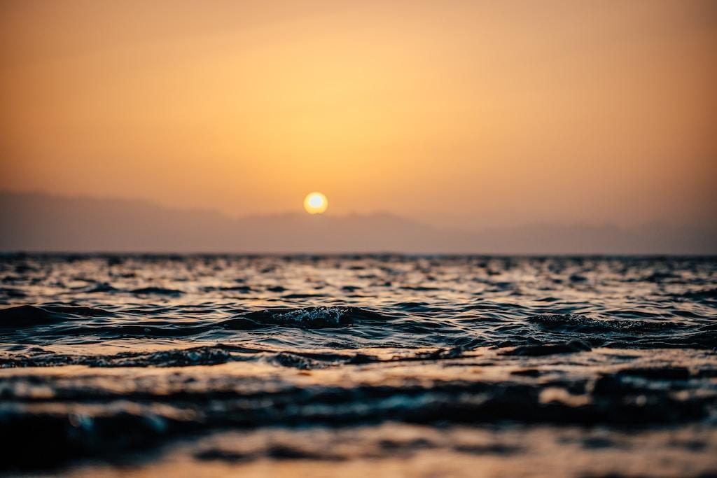 ocean waves under orange sunset
