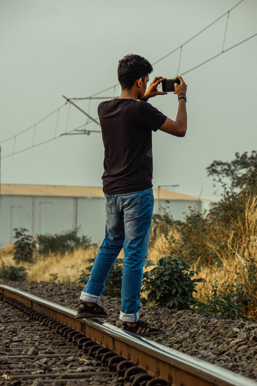man in black t-shirt and blue denim jeans holding black dslr camera