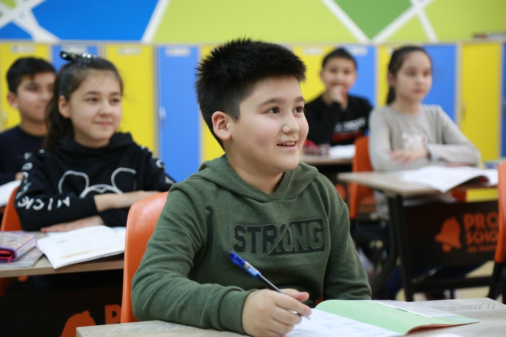 boy in gray long sleeve shirt holding pen