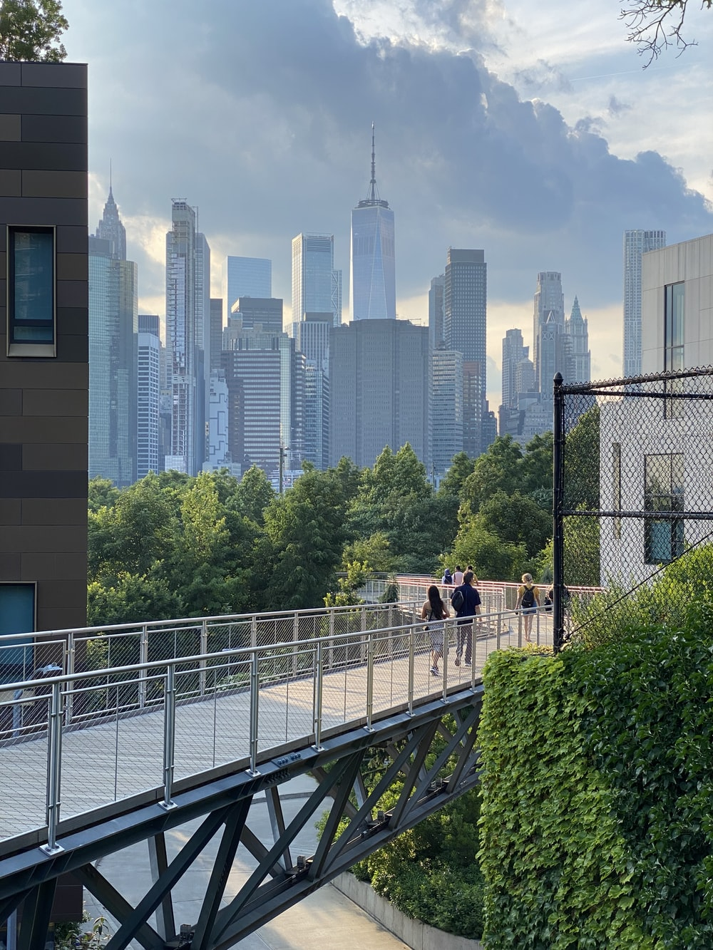 people walking on bridge near high rise buildings during daytime
