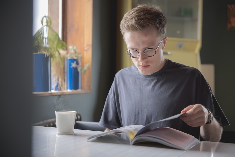 boy in blue crew neck shirt wearing eyeglasses reading book