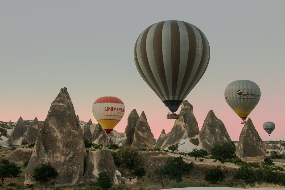 red and white hot air balloons on mid air during daytime