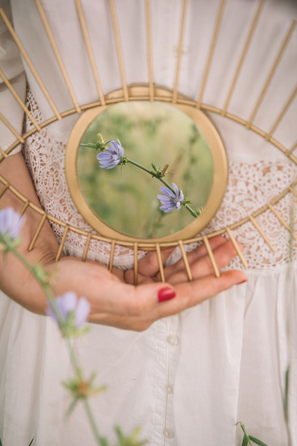 person holding gold framed round mirror