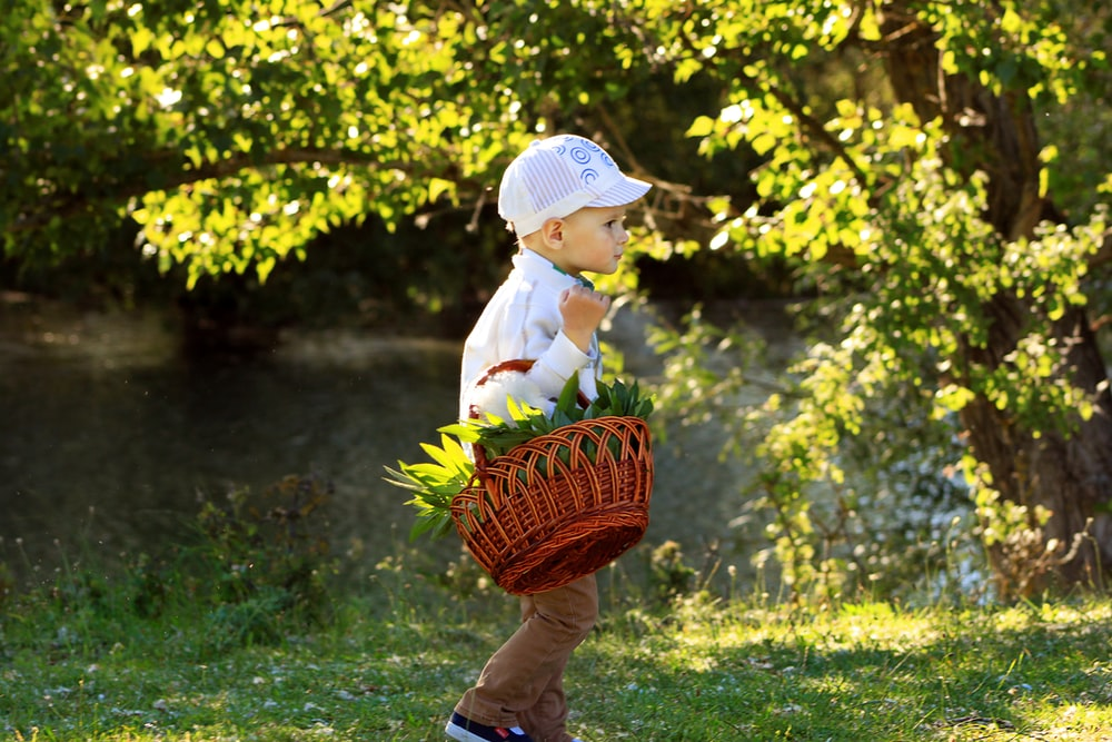 child in white long sleeve shirt and white hat holding basket