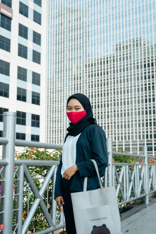woman in black hijab standing near white metal railings