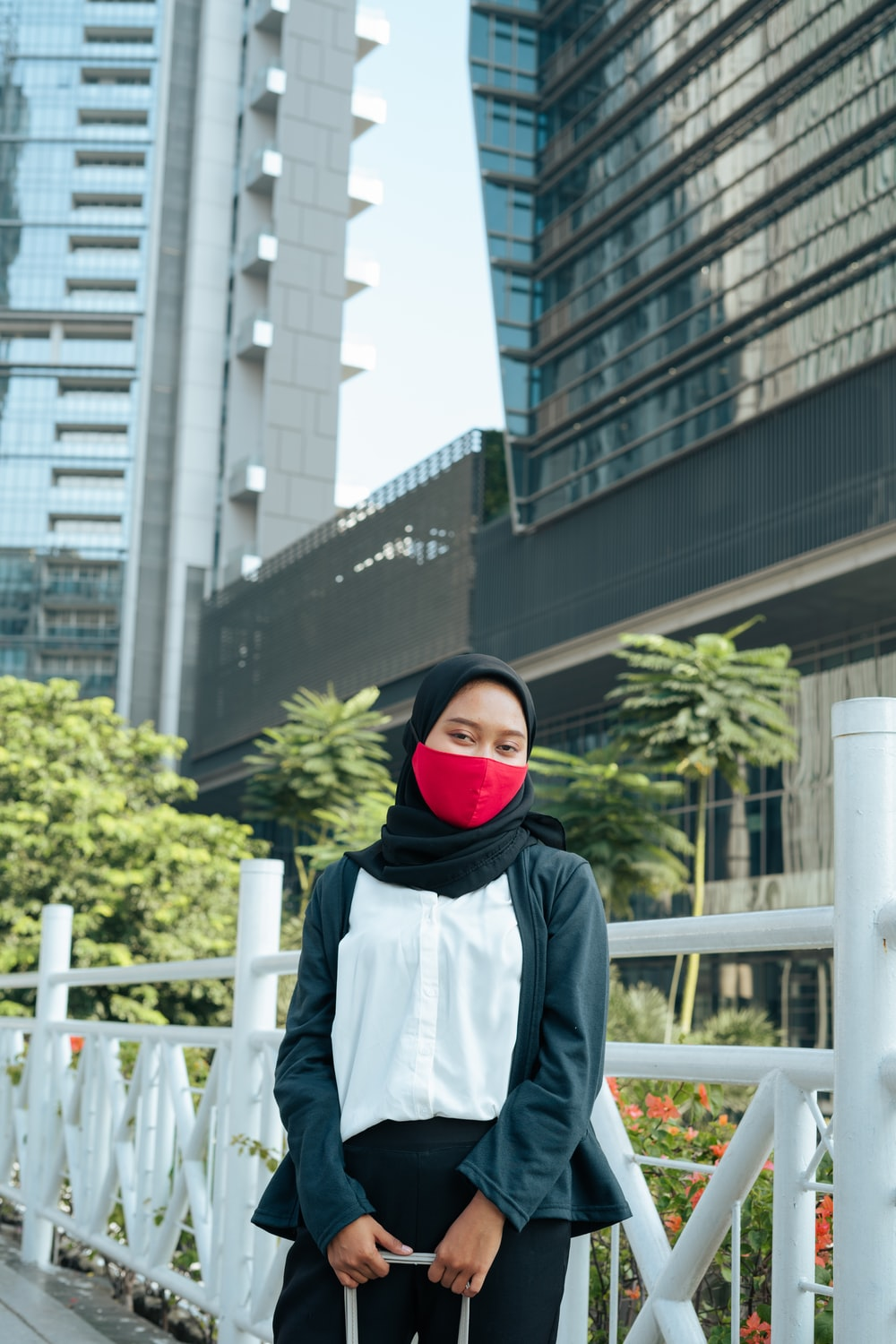woman in black hijab standing near white metal fence during daytime