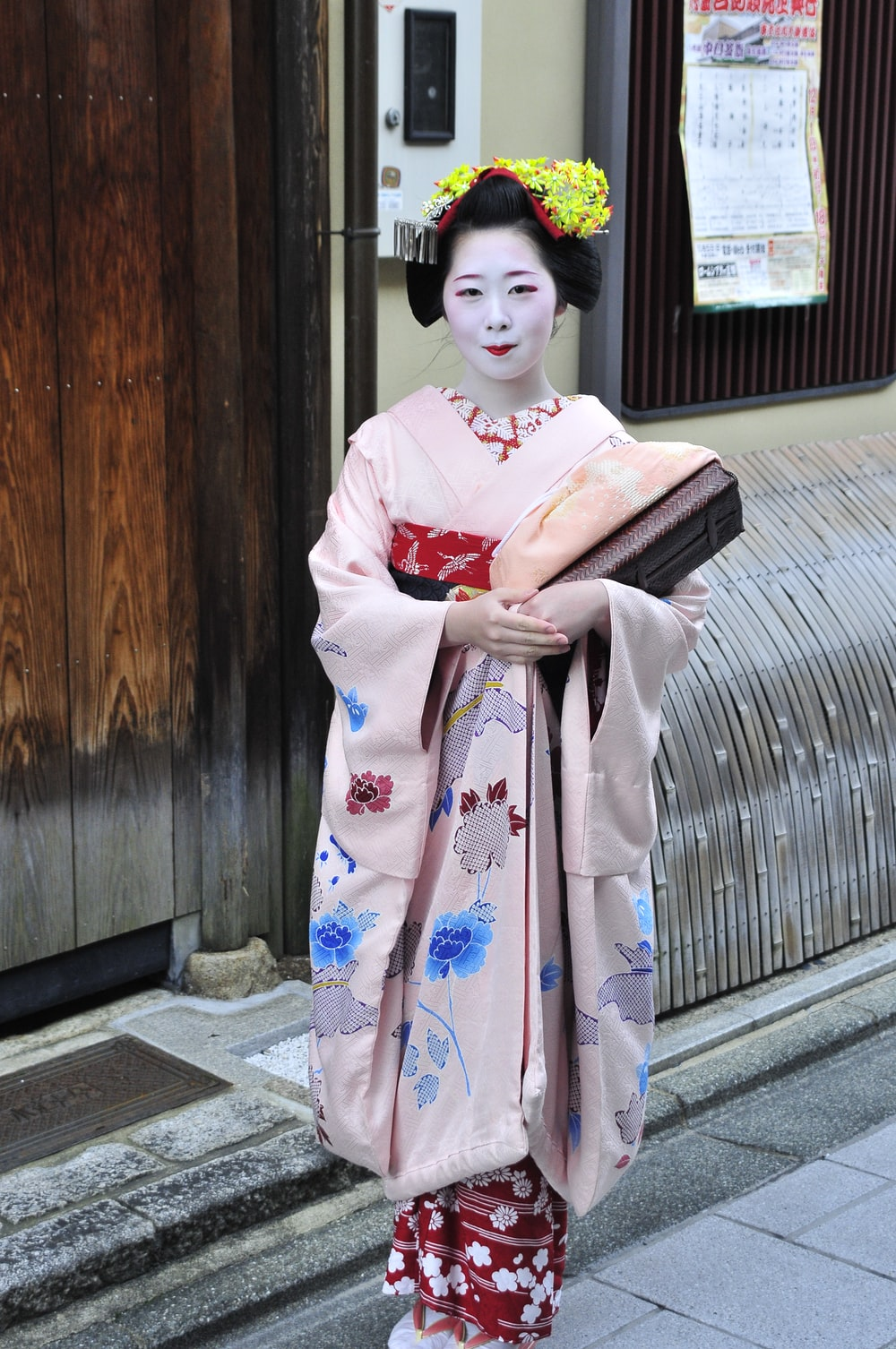 woman in kimono standing on sidewalk